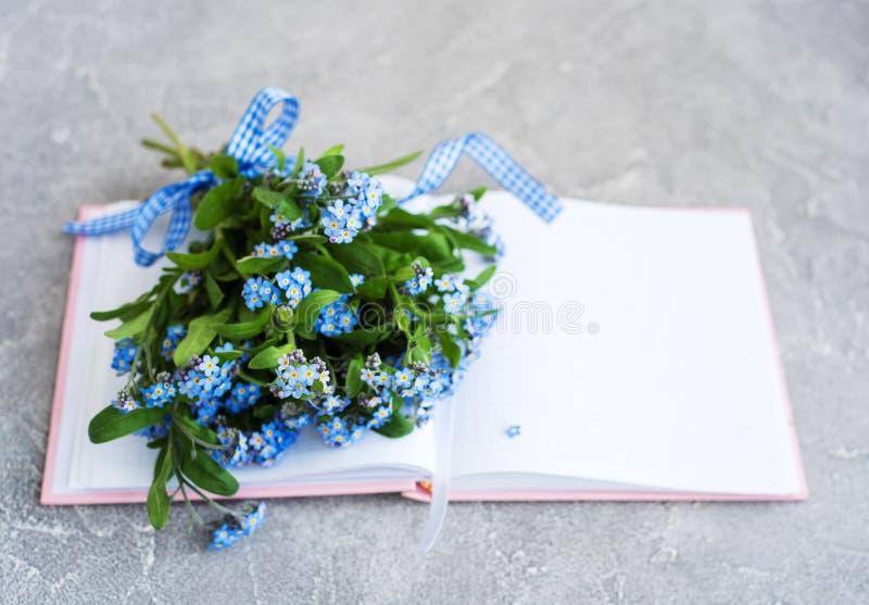 Vergeet me niet bloemen en notitieboekje stock foto