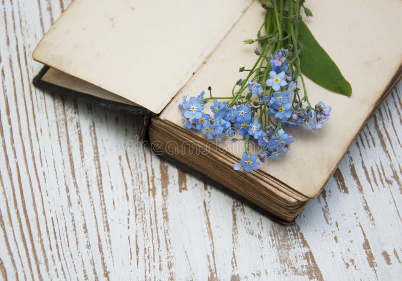 Vergeet-mij-nietjesbloemen en oud boek royalty-vrije stock afbeeldingen