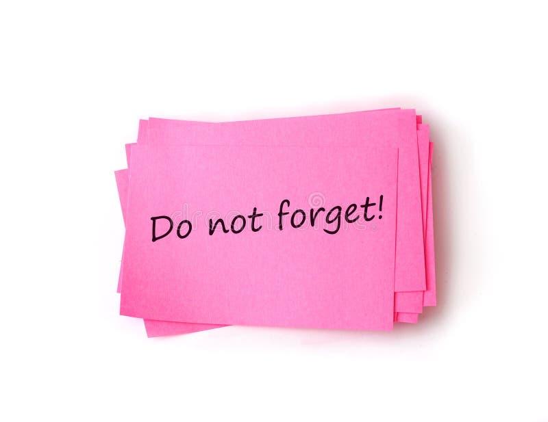 Vergeet niet op kleverige die Nota op wit wordt geïsoleerd stock foto's