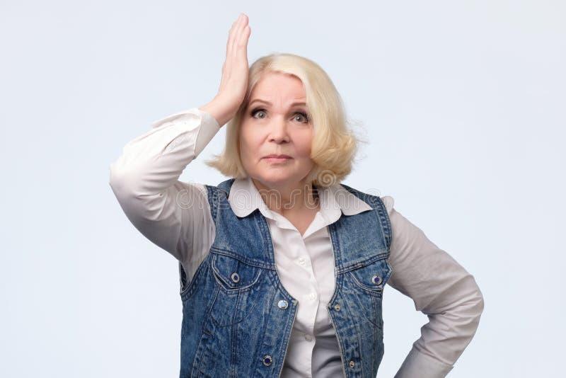 Vergeetachtige bejaarde blondevrouw die haar hoofd krassen stock foto