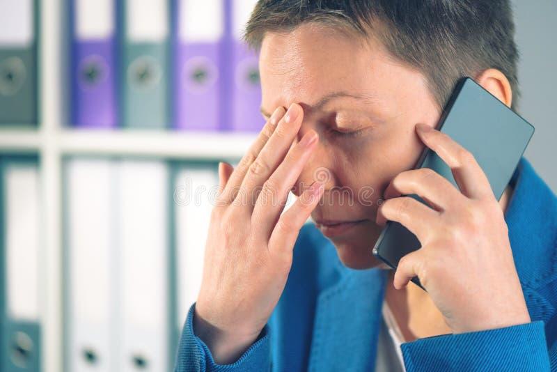 Vergeetachtige onderneemster tijdens mobiel telefoongesprek stock foto's