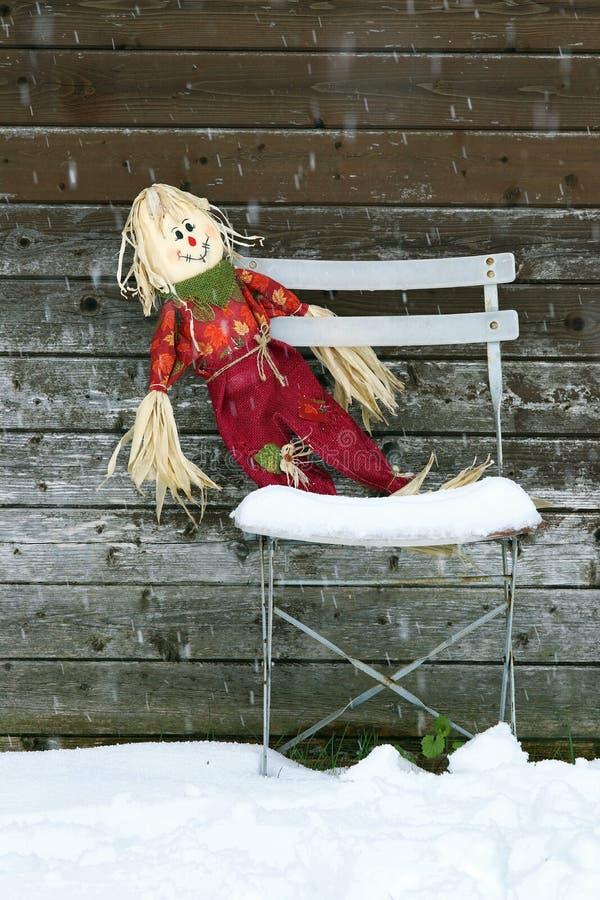 Vergessene Puppe auf dem alten Stuhl im Winter stockfotografie