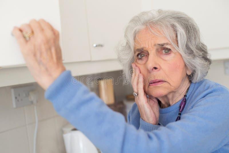 Vergessliche ältere Frau mit der Demenz, die im Schrank schaut stockfotografie