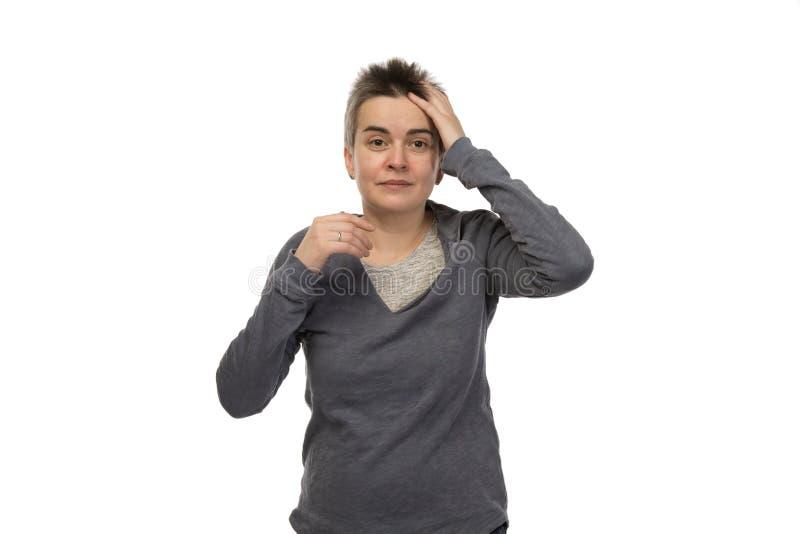 Vergessliche brunette weiße Frau mit dem kurzen Haar, das ihren schmerzenden Kopf hält Getrennt auf weißem Hintergrund stockfotografie