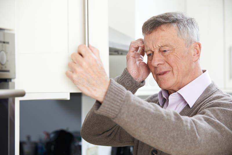 Vergesslicher älterer Mann, der im Schrank schaut lizenzfreie stockbilder