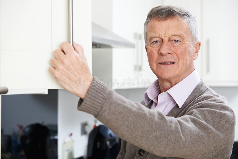 Vergesslicher älterer Mann, der im Schrank schaut lizenzfreies stockfoto