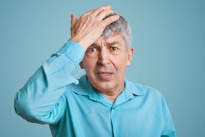 Vergesslicher hübscher elederly geknitterter Mann im blauen Hemd, hält Hand auf Kopf, sich fühlt hoffnungslos wie vergisst über w lizenzfreies stockfoto