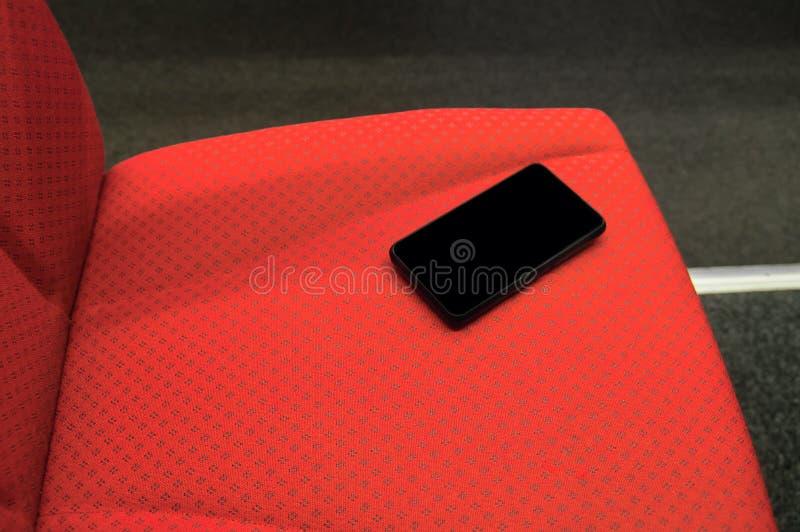 Vergeten smartphone met het lege zwarte scherm op de rode stoel van een hogesnelheidstrein Conceptenreis en verloren gadgets stock fotografie