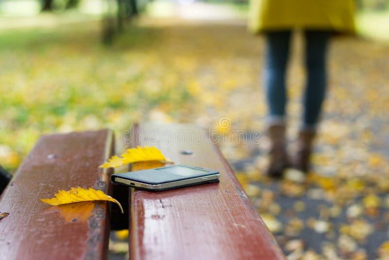 Vergeten smartphone op een parkbank royalty-vrije stock afbeeldingen