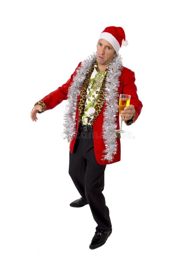 Vergeudeter getrunkener älterer Geschäftsmann der Rührstange in der Champagne Christmas-Toastpartei bei der Arbeit, die Sankt-Hut stockfoto
