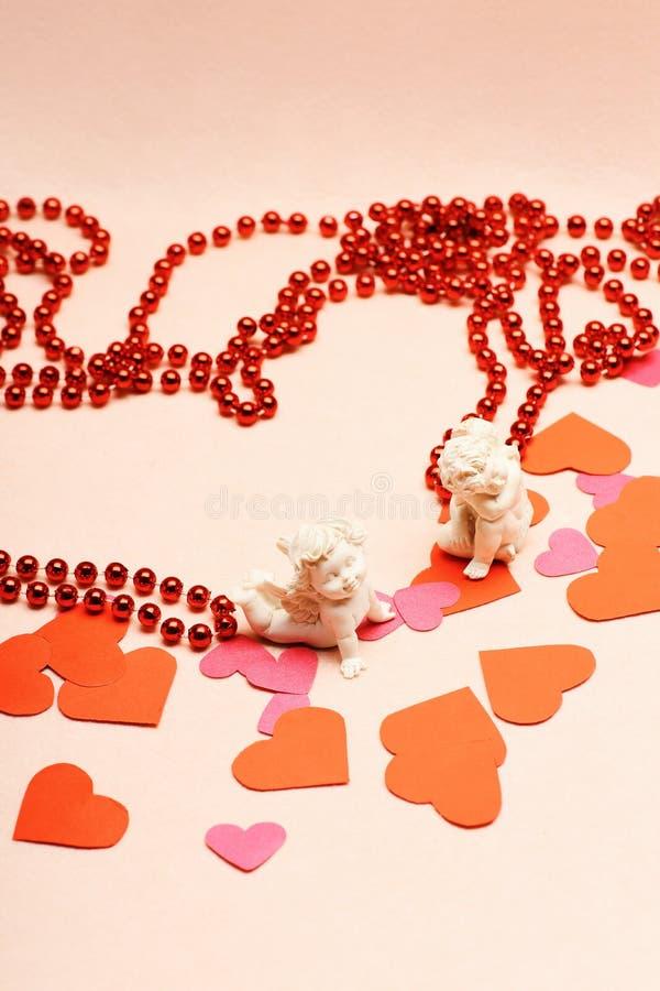 Vergipsen Sie Amoren mit Herzen und roten Perlen, Liebeskonzept stockfoto