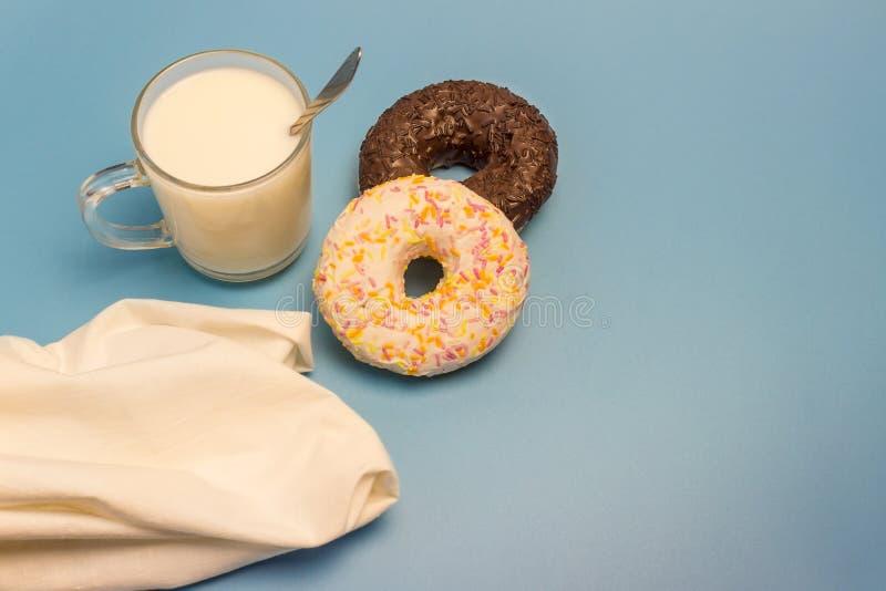 Verglaasd donuts, melk, lepel en servet op een blauwe achtergrond royalty-vrije stock foto