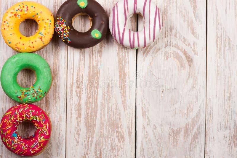 Verglaasd donuts op een witte houten achtergrond met exemplaarruimte voor uw tekst Hoogste mening stock fotografie