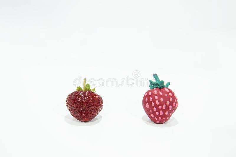 Vergleich von zwei Erdbeeren - wirklich und gefälscht lizenzfreies stockfoto