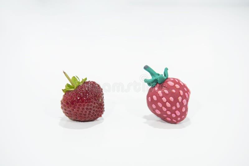 Vergleich von zwei Erdbeeren - wirklich und gefälscht lizenzfreie stockfotos