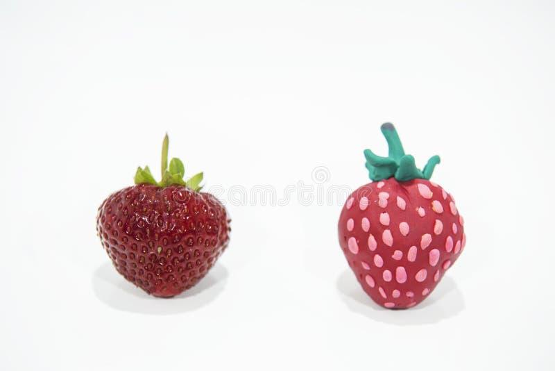 Vergleich von zwei Erdbeeren - wirklich und gefälscht stockbilder