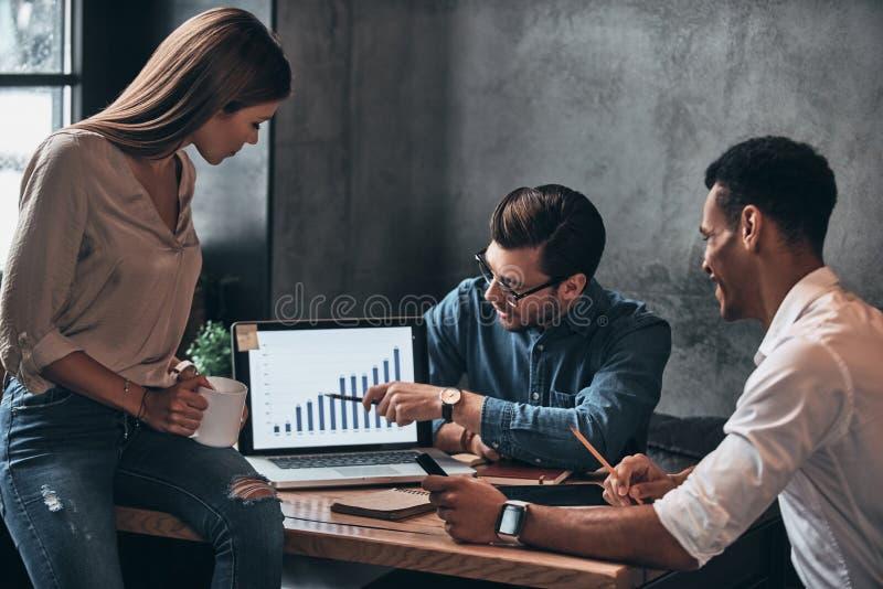 Vergleichen von Verkäufen Gruppe junge überzeugte Geschäftsleute Diskus lizenzfreie stockfotos