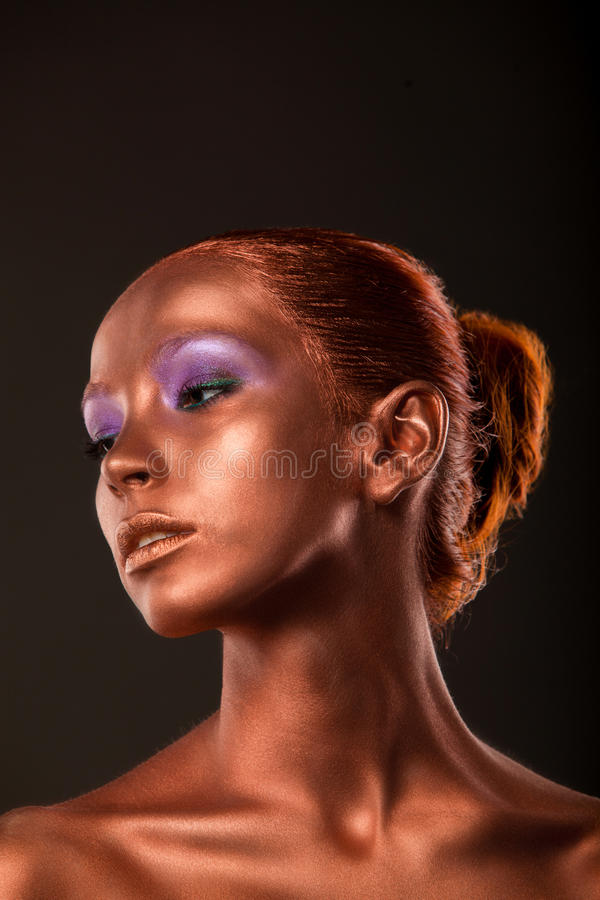 vergoldung Das Gesichts-Nahaufnahme der goldenen Frau Futuristisches vergoldetes Make-up Gemalte Hautbronze stockbild