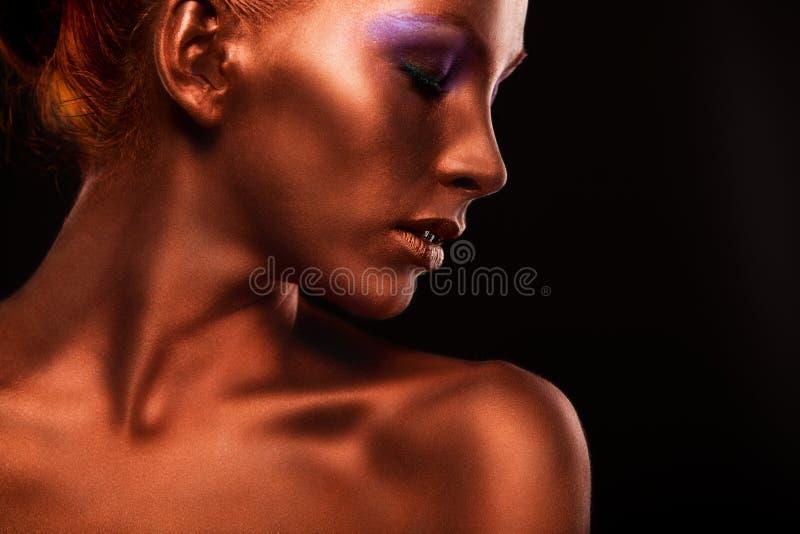 vergoldung Das Gesichts-Nahaufnahme der goldenen Frau Futuristisches vergoldetes Make-up Gemalte Hautbronze stockbilder