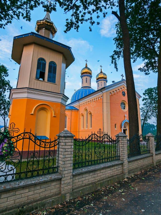 Vergoldung von Kirchenhauben mit Kreuzen auf dem Dach der Kirche, die hinter einem niedrigen Zaun mit einem gebogenen Zaun steht stockfotos