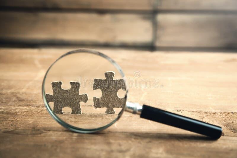Vergrößerungsglas überprüft Puzzlespiele Die goldene Taste oder Erreichen für den Himmel zum Eigenheimbesitze lizenzfreie stockfotografie