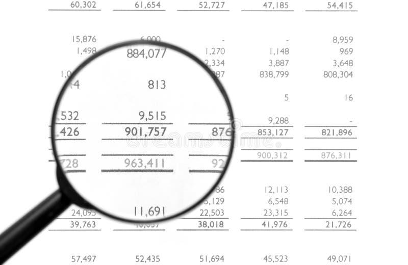 Vergrößerungsglas auf Finanzbilanz stockfotografie