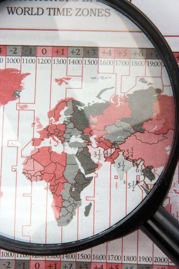 Vergrößerungsglas auf Weltkarte lizenzfreies stockbild