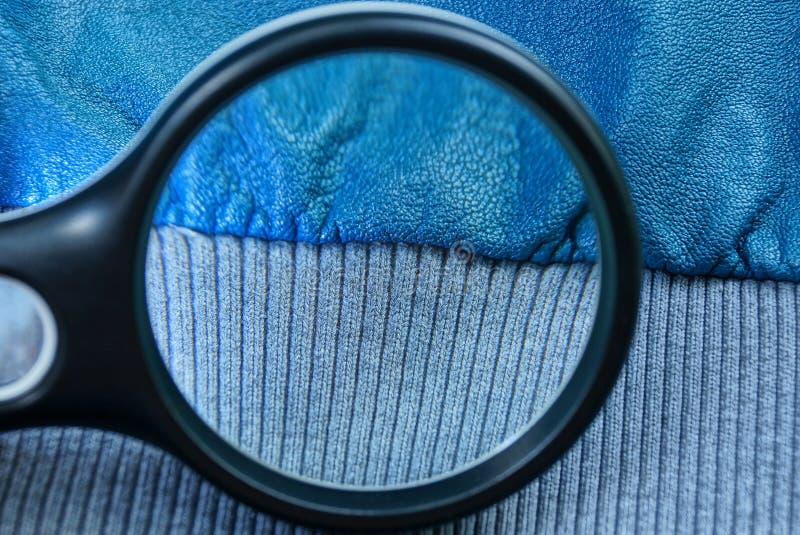 Vergrößerungsglas erhöht blaue Haut und graues Gewebe auf einem Kleidungsstück lizenzfreie stockfotografie