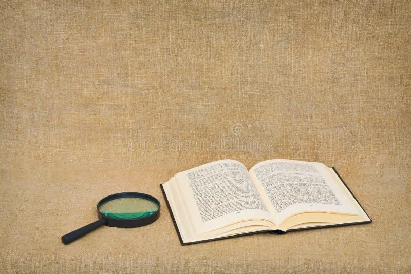 Vergrößerungsglas und geöffnetes Buch liegen gegen ein braunes Segeltuch stockbilder