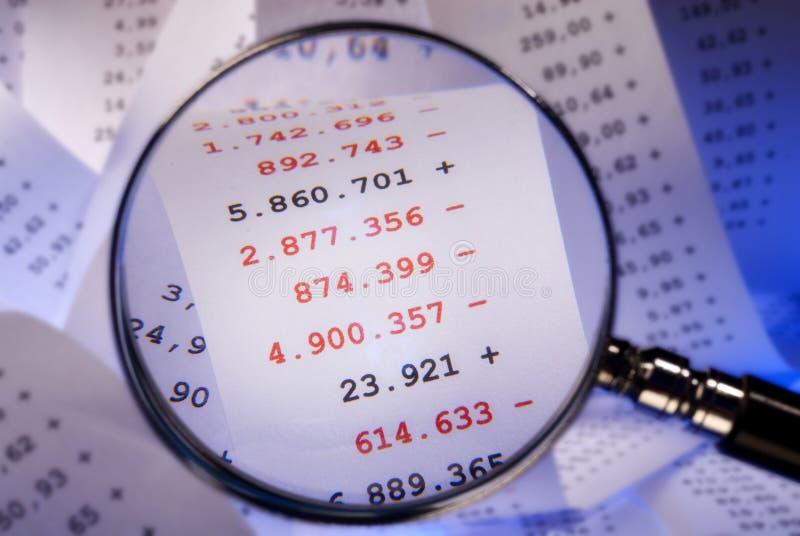 Vergrößerungsglas und rote Zahlen stockfotografie