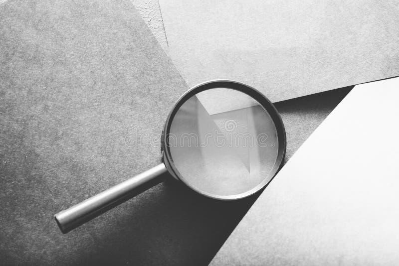 Vergrößerungsglassuchsuchvorgangblickneuzugang-Graupapier lizenzfreie stockbilder