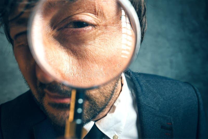 Vergroot oog van belastingsinspecteur het kijken door vergrootglas royalty-vrije stock fotografie