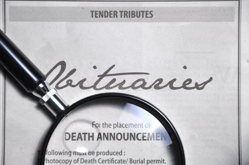 Vergrootglas en overlijdensberichtenreclame op krant stock foto