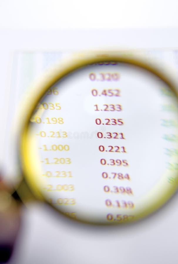Vergrootglas op financieel verslag stock foto's