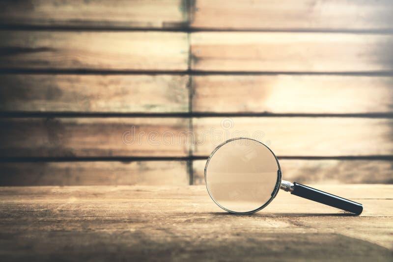 Vergrootglas op houten lijst Zoek en ontdekt stock foto's
