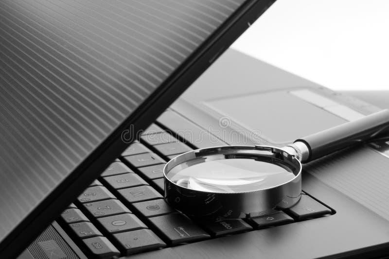 Vergrootglas op laptop computer stock afbeeldingen