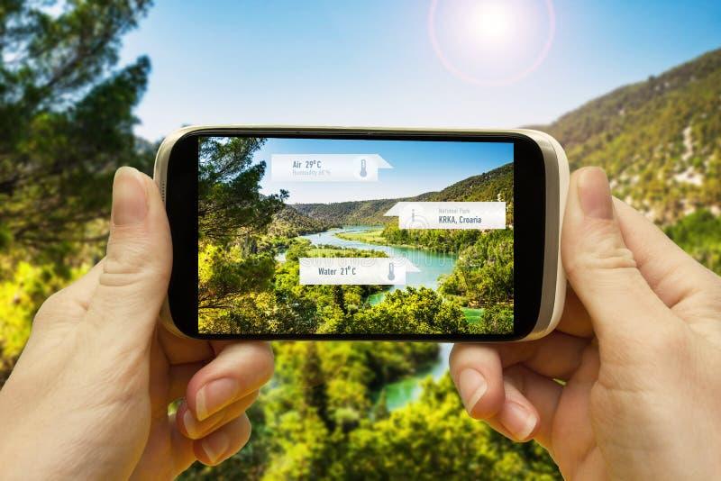 Vergrote werkelijkheidstoepassingen voor reis en vrije tijd Hand met een smartphone app A/informatie de op scherm van R over de p stock fotografie