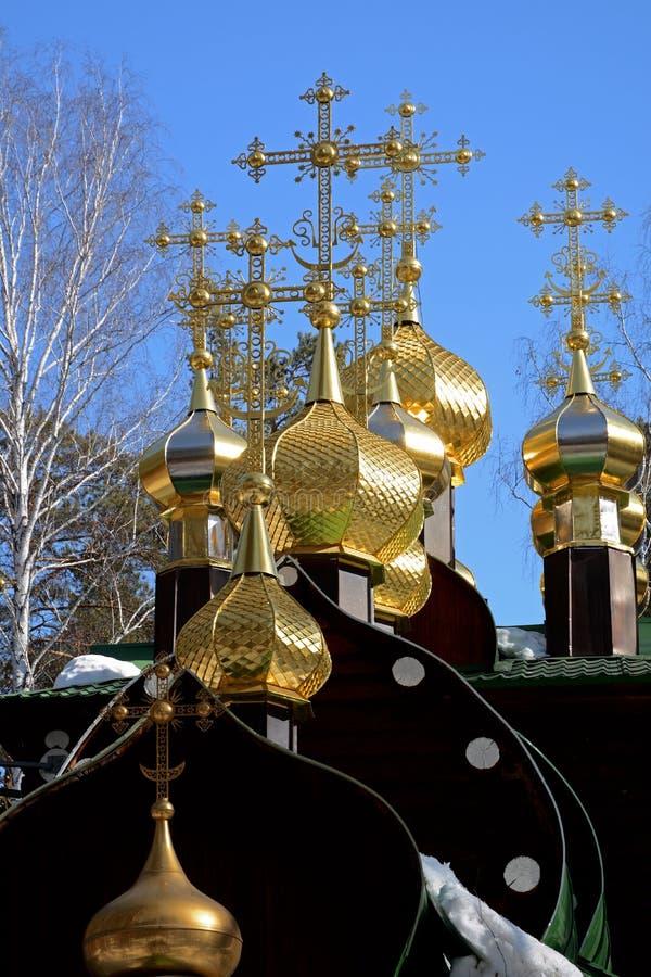 Vergulde koepels met kruisen van houten Russisch Orthodox Christian Church van Sinterklaas in het Klooster van Ganina Yama stock fotografie