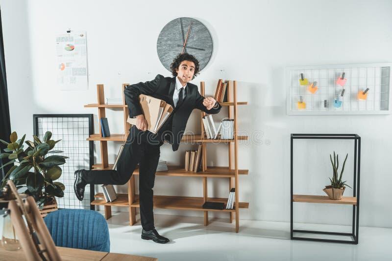 verhaastend zakenman met omslagen die in bureau lopen om uiterste termijn niet te missen royalty-vrije stock foto's
