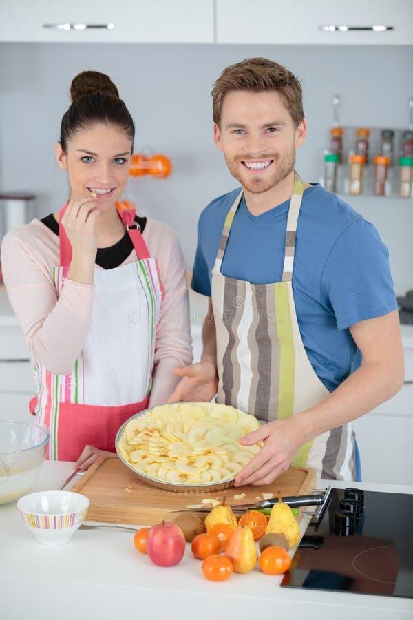 Verheiratetes Paar, das Apfelkuchen auf Küche macht lizenzfreie stockfotos