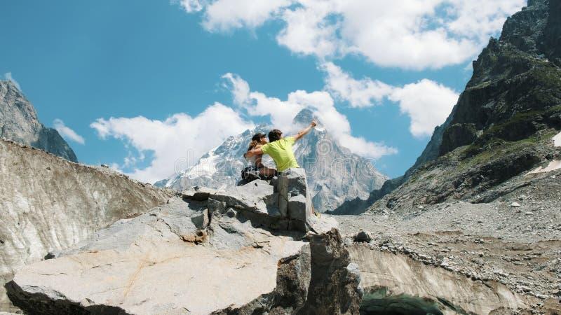 Verheiratetes Paar von Touristen sitzen auf einem Felsen und bewundern den Bergblick Mann umarmt eine Frau in einer Wanderung lizenzfreie stockbilder