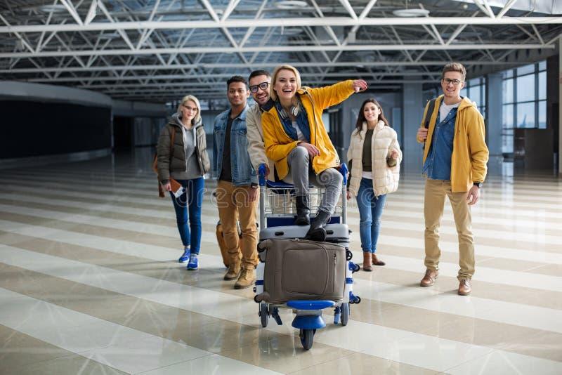 Verheugende reizigers met bagagekarretje het gaande inschepen royalty-vrije stock afbeelding