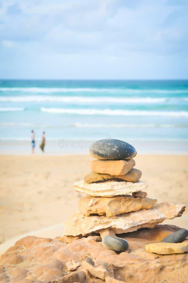 Verhoudingsconcept met stapel van rotsen en mensen op de achtergrond stock afbeelding