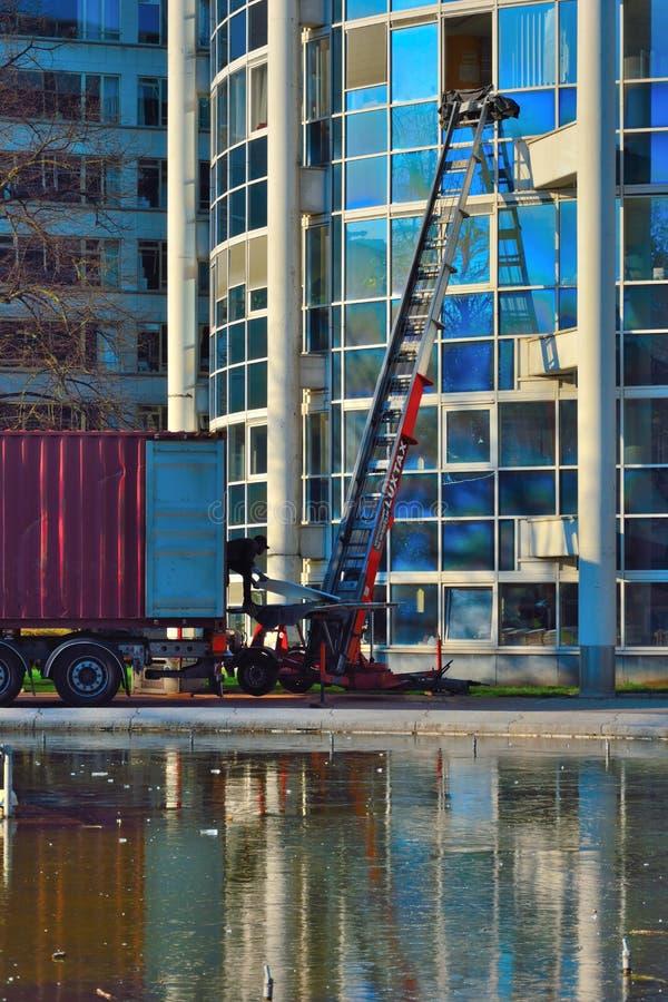 Verhuiswagen en mens die voor een verhuizing, een nieuw begin werken stock afbeeldingen