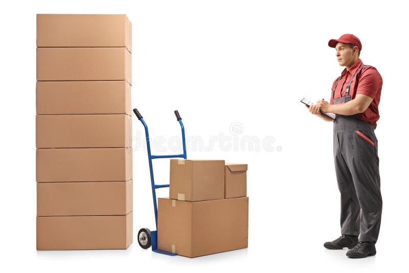 Verhuizer die stapels dozen bekijken en in klembord schrijven stock foto