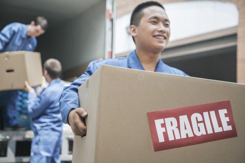 Verhuizers die een verhuiswagen leegmaken en een breekbare doos dragen stock foto's