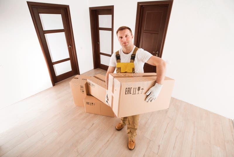 Verhuizersmens die grote doos van punten in lege flat houden stock afbeeldingen