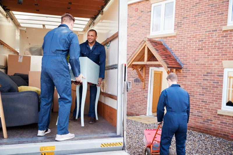 Verhuizing van de werknemers van het bedrijf die meubilair en dozen van vrachtwagen naar nieuwe huis op de dag van het vervoer lo royalty-vrije stock foto's