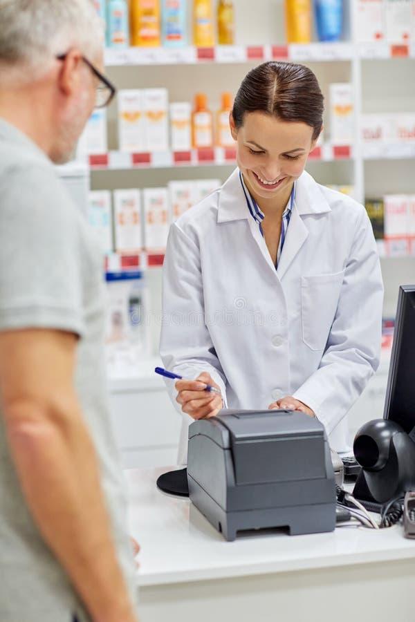 Verificação da escrita do farmacêutico para o cliente na drograria fotos de stock royalty free