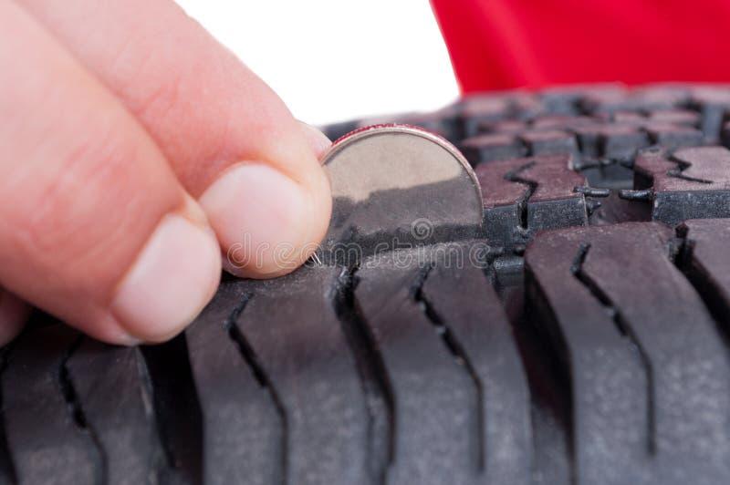 Verificação da profundidade do pneu de carro com moeda fotografia de stock